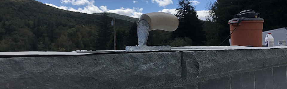 Pool trowel resting on bluestone pool coping.